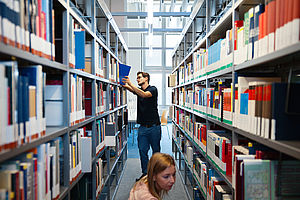 Shelves in the library Campus Wilhelminenhof with a Person looking for literature